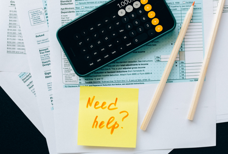 Tax forms and calculator with a post-it reading Need Help?